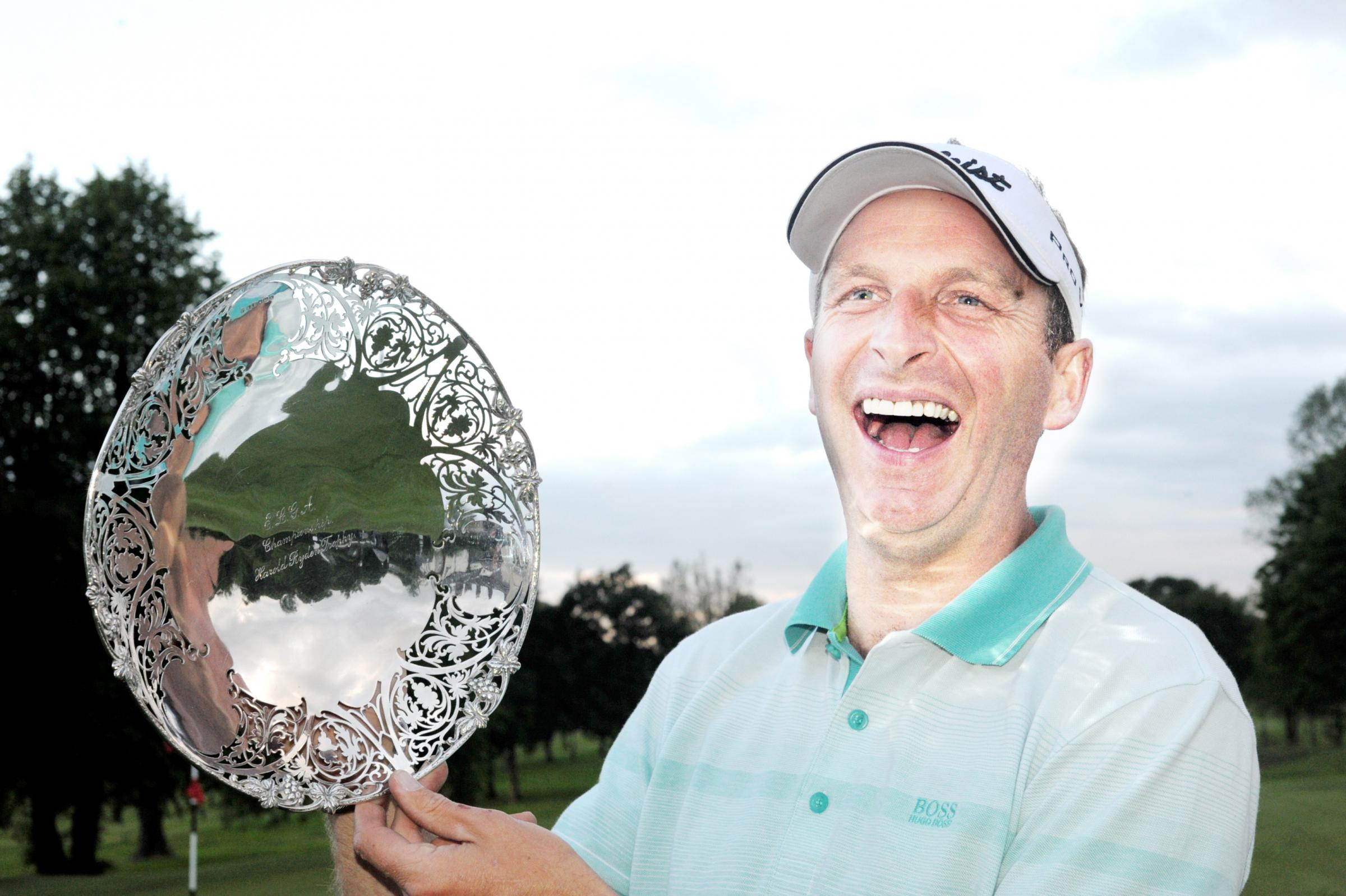 TRIUMPH: Michael Hunt celebrates with the Harold Ryden Trophy after a victory over Blackburn's Anthony Harwood on his home course of Pleasington on Wednesday night