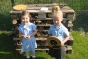 CHECK IN? Jasmine and Poppy with the bug hotel that a parent helped build
