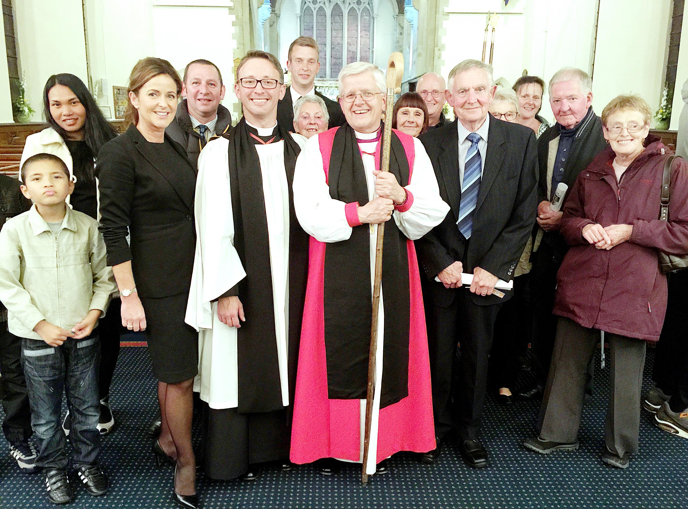 WELCOME: Rt Rev. Julian Henderson and Rev Toby Webber, centre, with some of Toby's new parishioners after the induction service