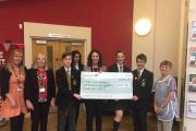 Volunteers at East Lancashire Hospice receiving the cheque from pupils at Mount Carmel in Accrington
