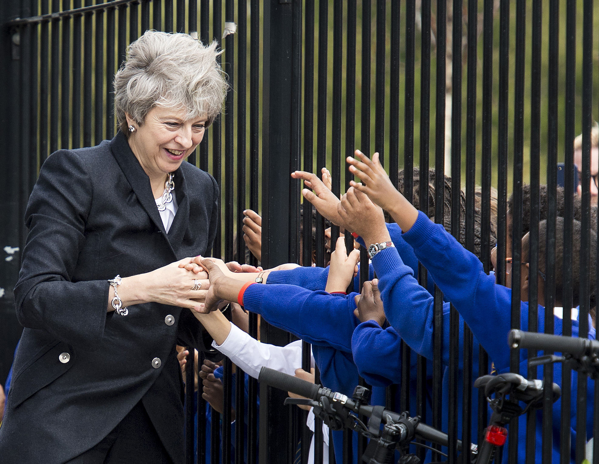 Embargoed to 2230 Monday October 9..Prime Minister Theresa May is greeted by primary pupils during a visit to the Dunraven School in Streatham, south London, ahead of the publication of details of the Government's Race Disparity Audit. PRESS ASSOCIATI