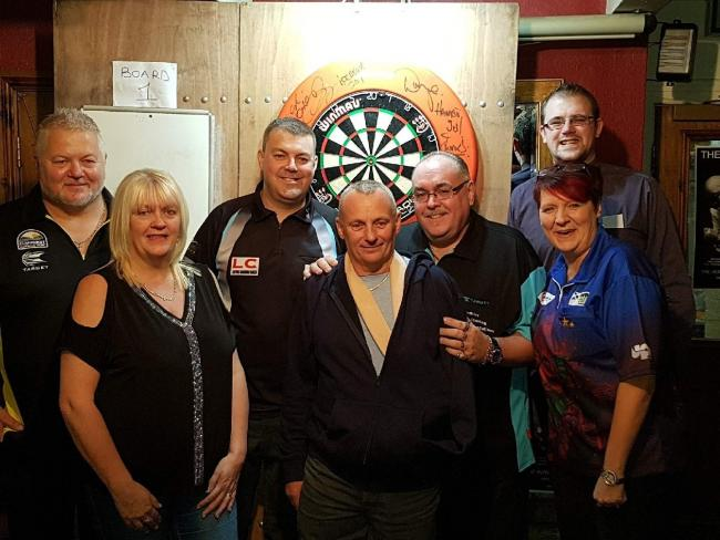Carole Davis is joined by darts players at  charity fundraiser