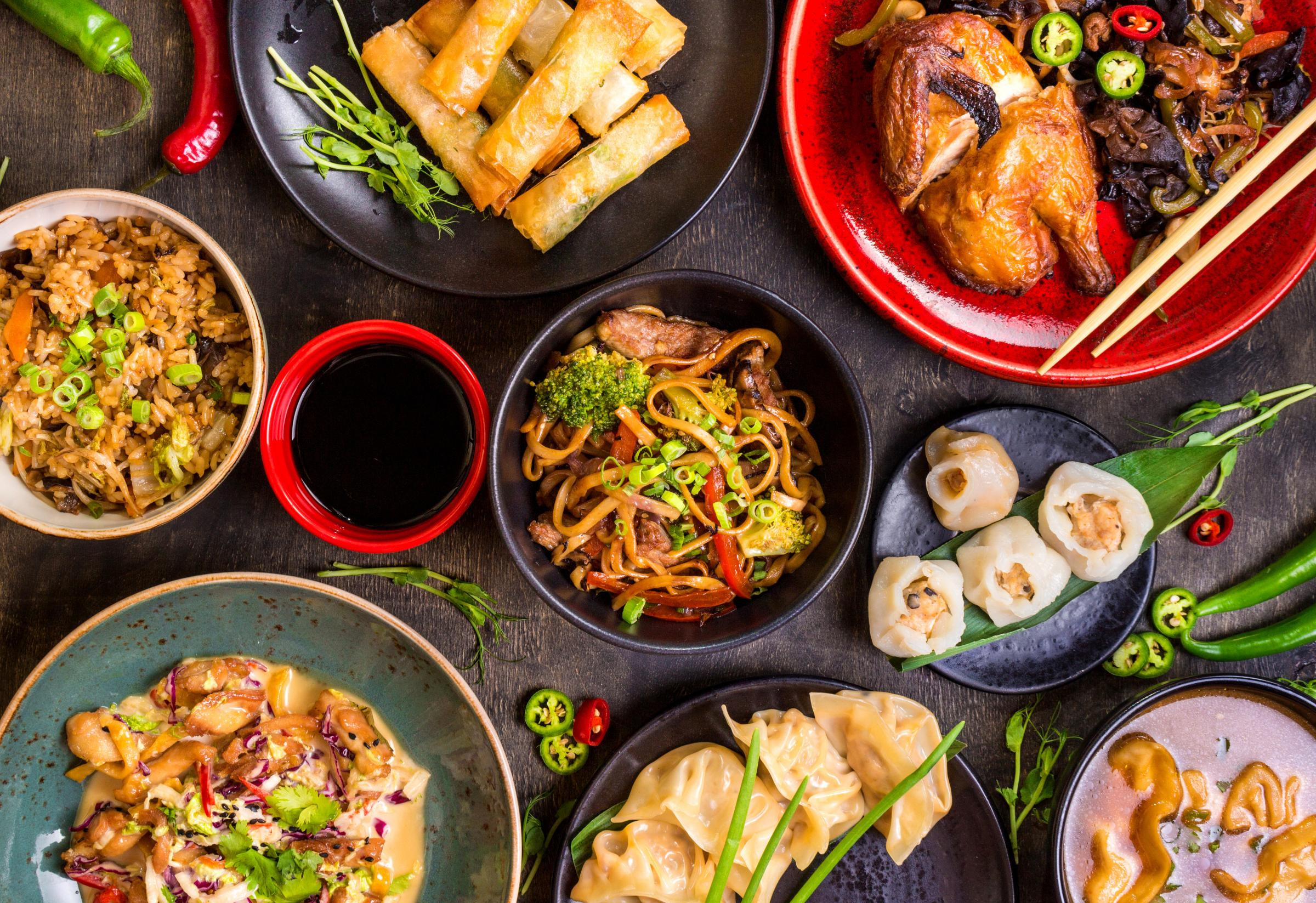 Assorted Chinese food set. Chinese noodles, fried rice, dumplings, peking duck, dim sum, spring rolls. Famous Chinese cuisine dishes on table. Top view. Chinese restaurant concept. Asian style banquet.