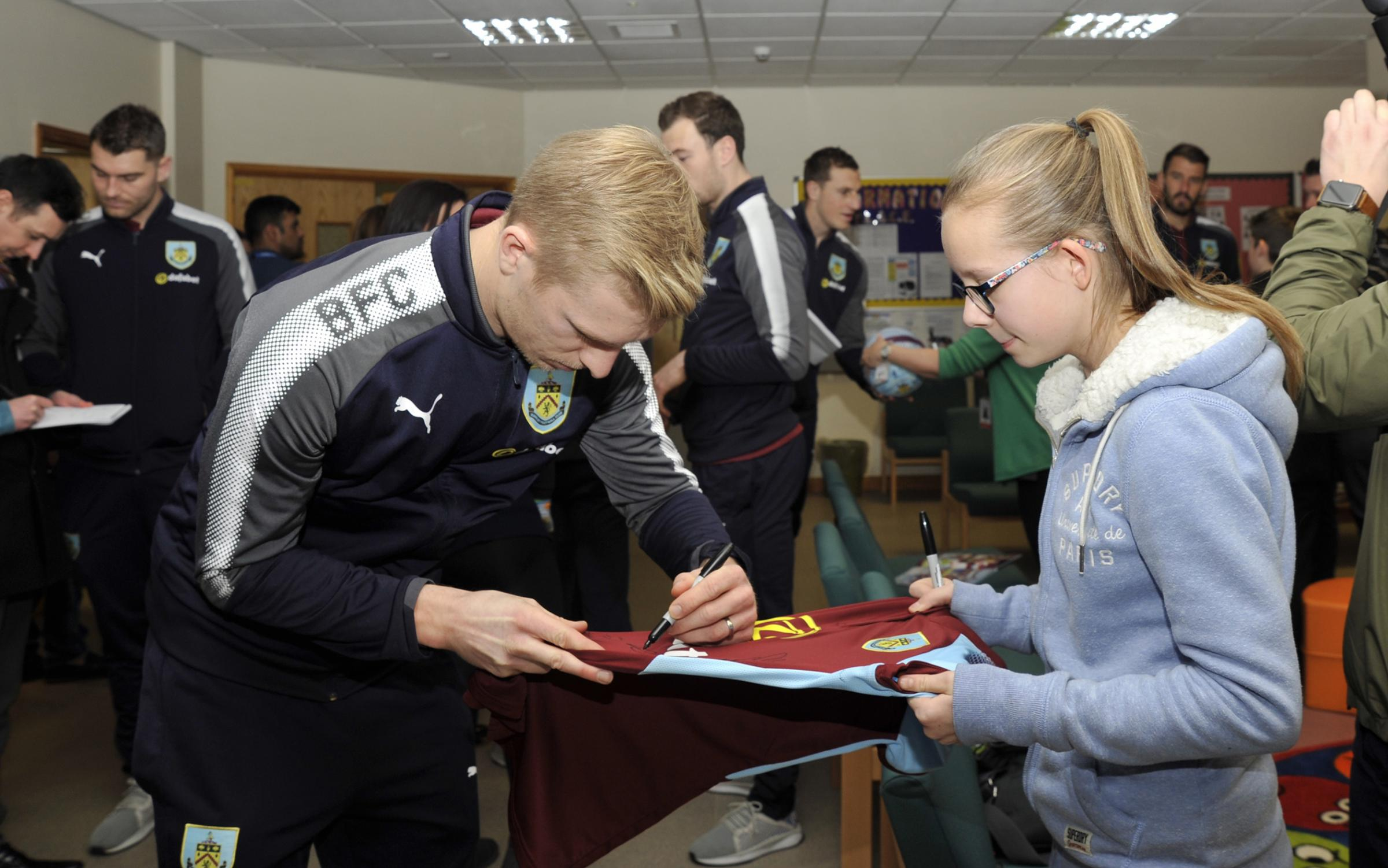 Ben Mee signs an autograph during a visit to Burnley General Hospital