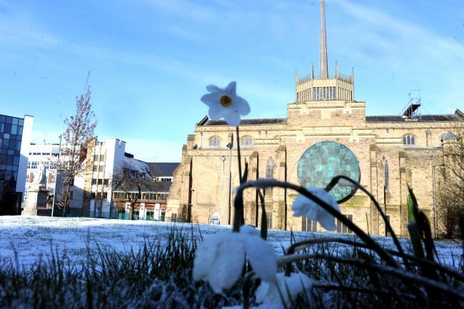 A layer of snow sits pretty on the daffodil grassy bank by Blackburn Cathedral