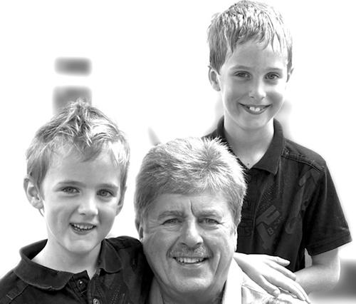 A happy David Grogan relaxing with two of his three grandchildren