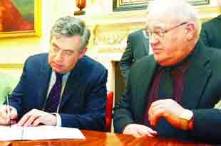 Write away: Gordon Brown puts pen to paper, watched by Coun Colin Rigby