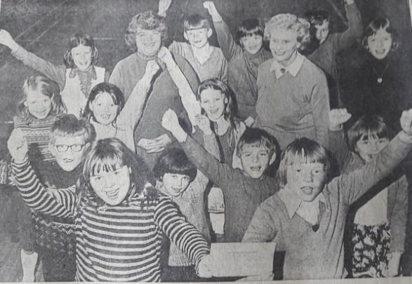 Christopher and Caroline (with the cheque) lead the cheers as some of the children surround Jean Tattersall (left) and Edna Riley