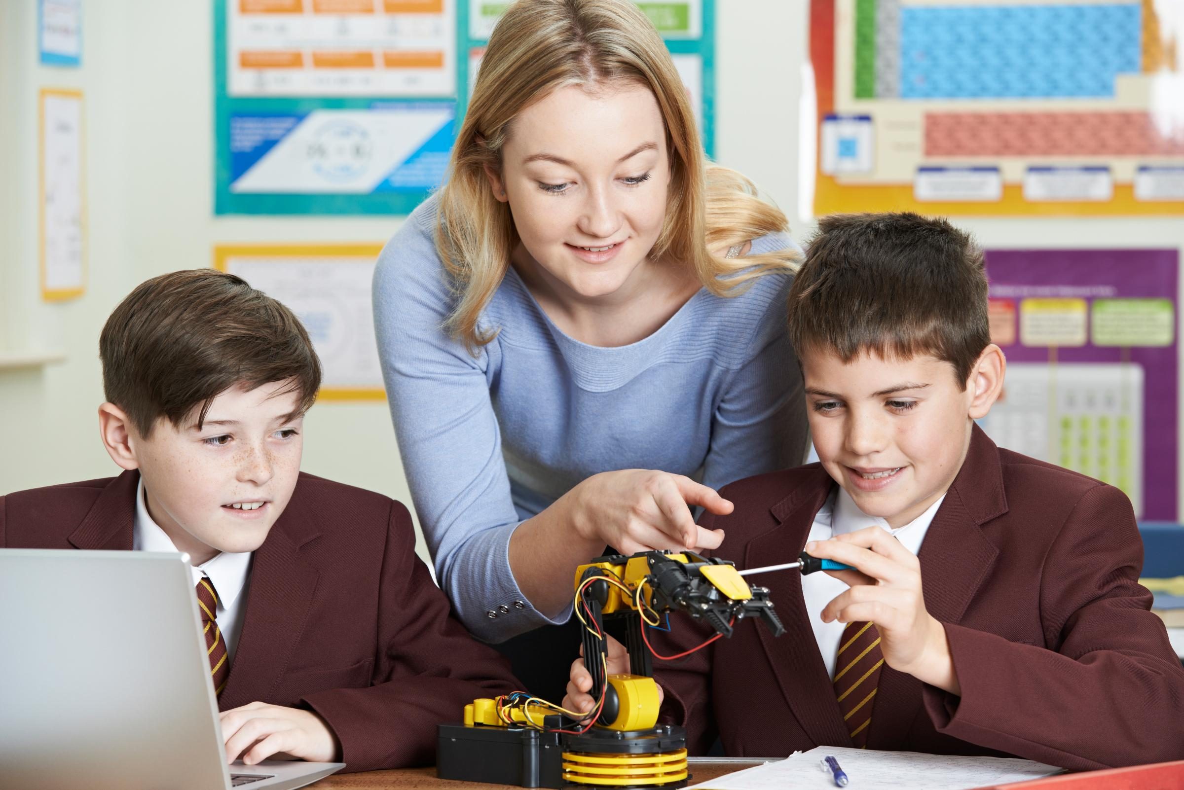 Teacher With Pupils In Science Lesson Studying Robotics.