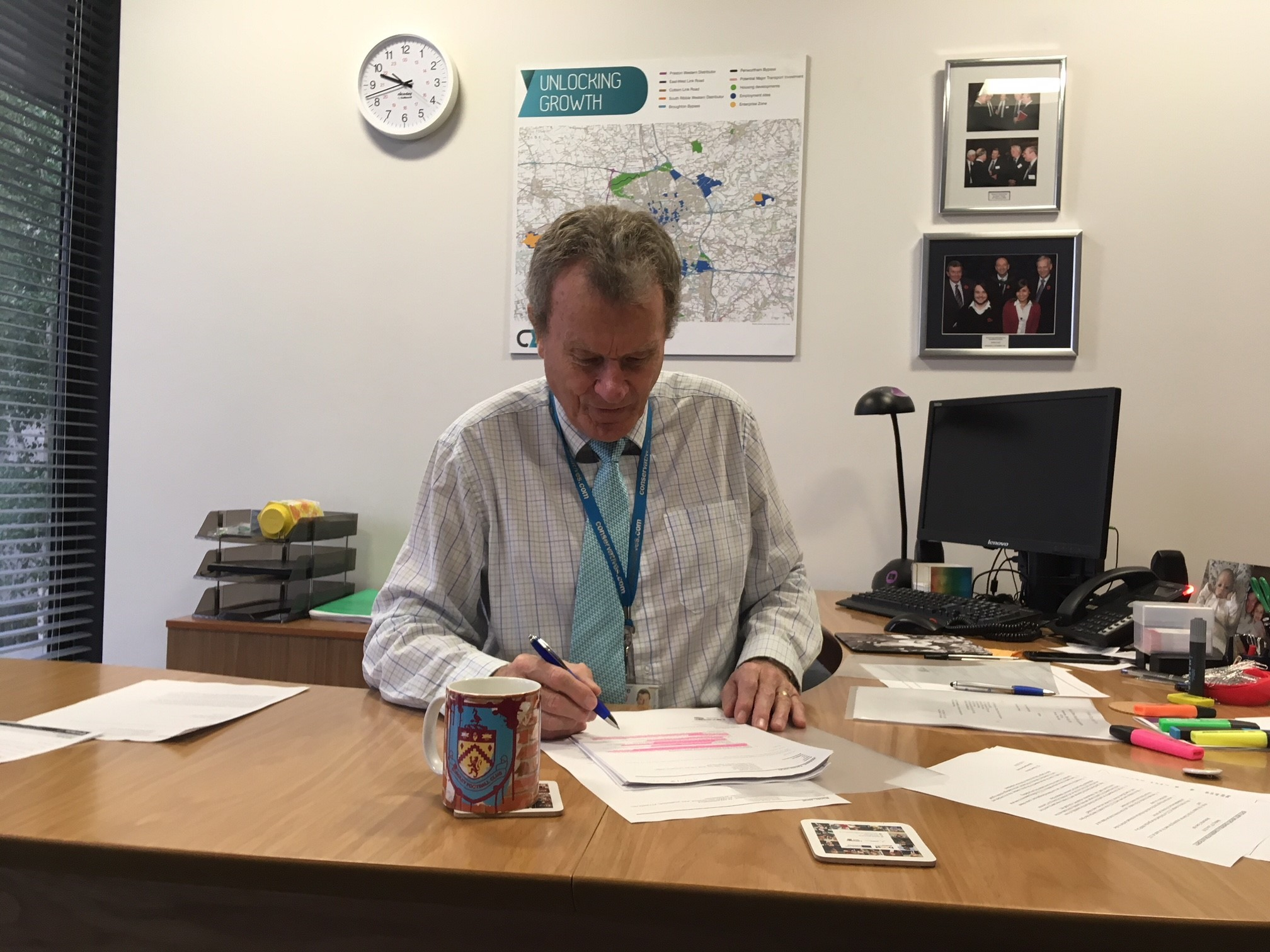 Geoff Driver at his desk with his Clarets mug and mousemat.