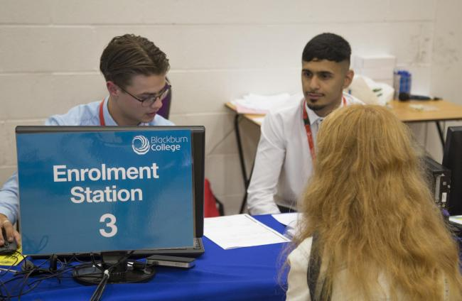 Blackburn College staff member Liam Cross and apprentice Ismaeel Hussain help a student enrol
