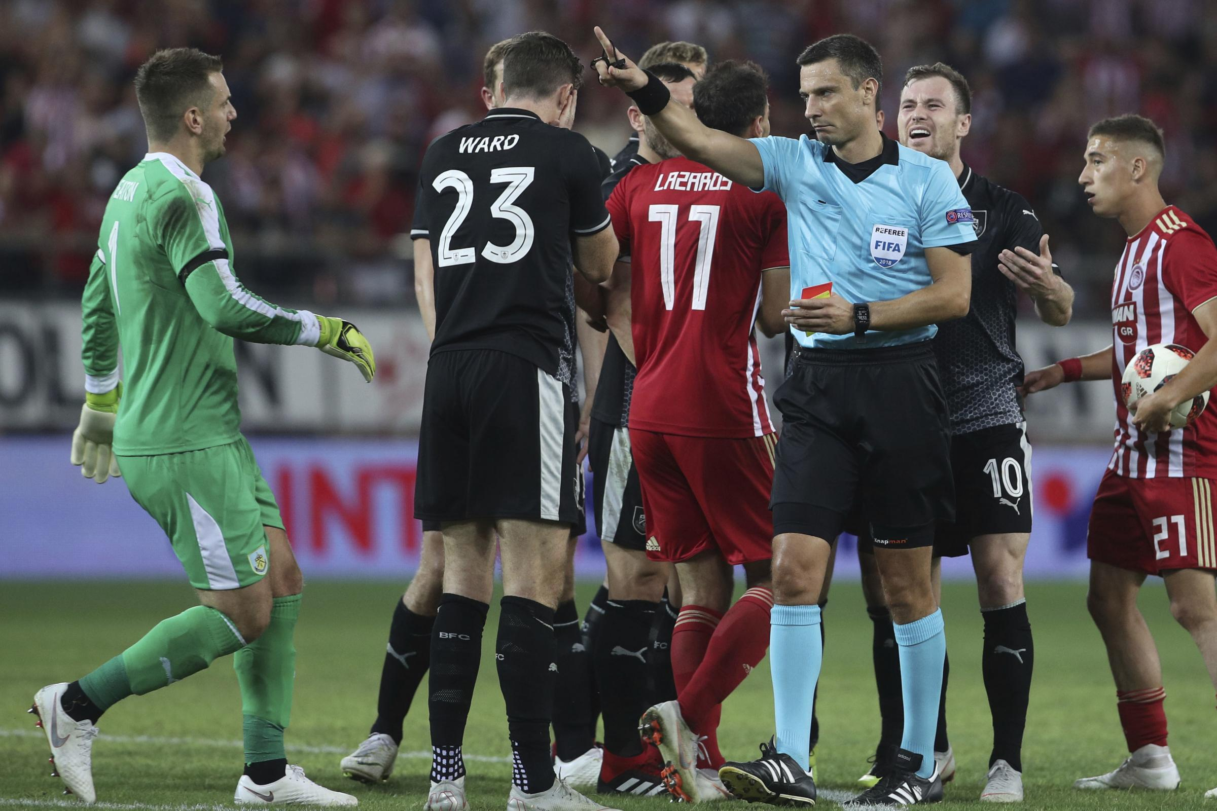 Referee Slavko Vincic gives a penalty to Olympiakos as Burnley's Ashley Barnes, second right, gestures during the Europa League playoffs, first leg, soccer match between Olympiacos Piraeus and Burnley at the Karaiskakis Stadium, in Athens, Greece, Thu