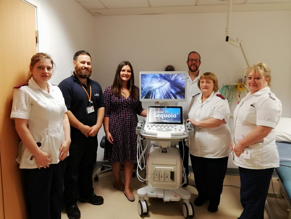 Hospital staff stand next to an ultrasound scanner