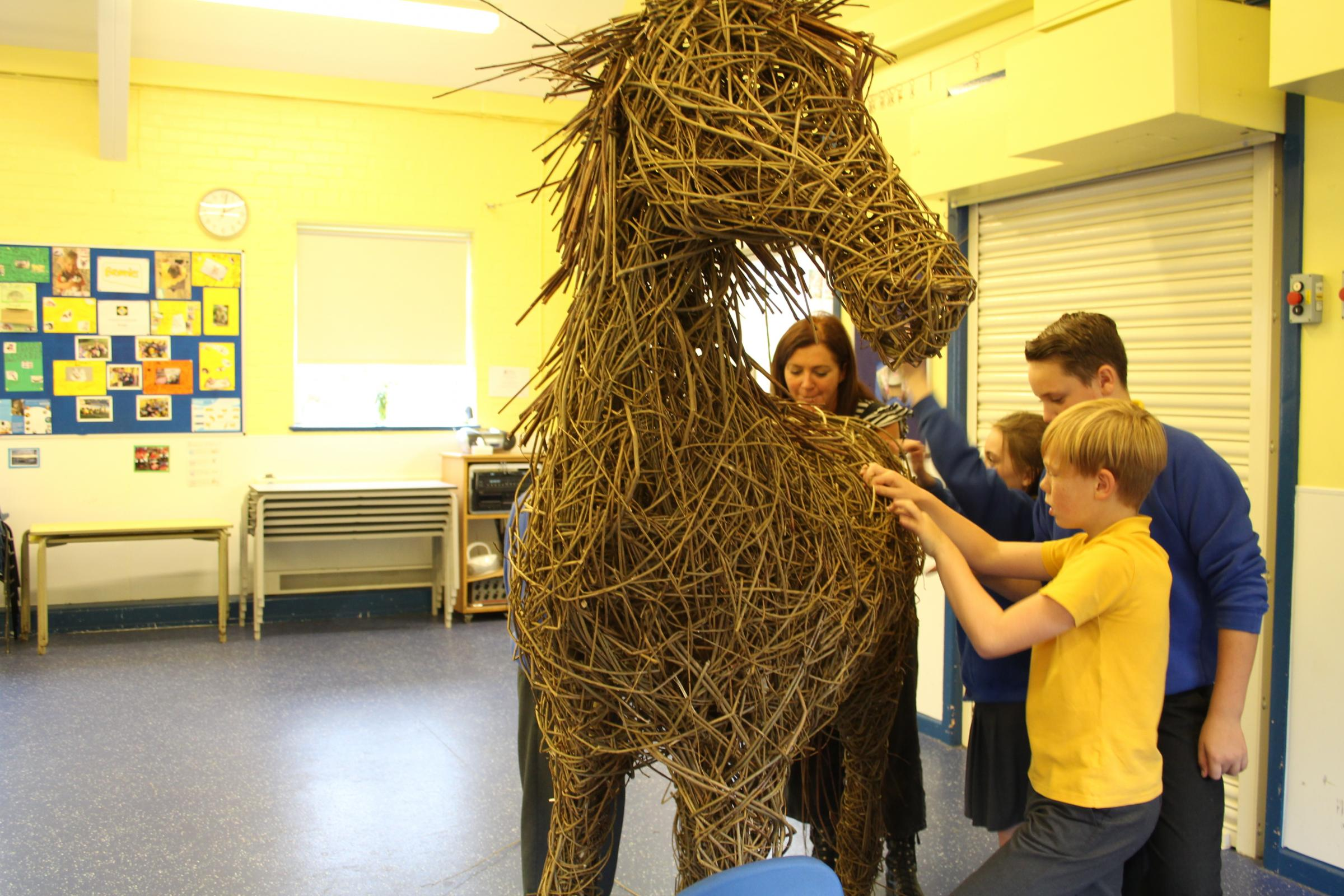 Students at St John's Church of England Primary School working to create a life sized war horse and large willow poppies