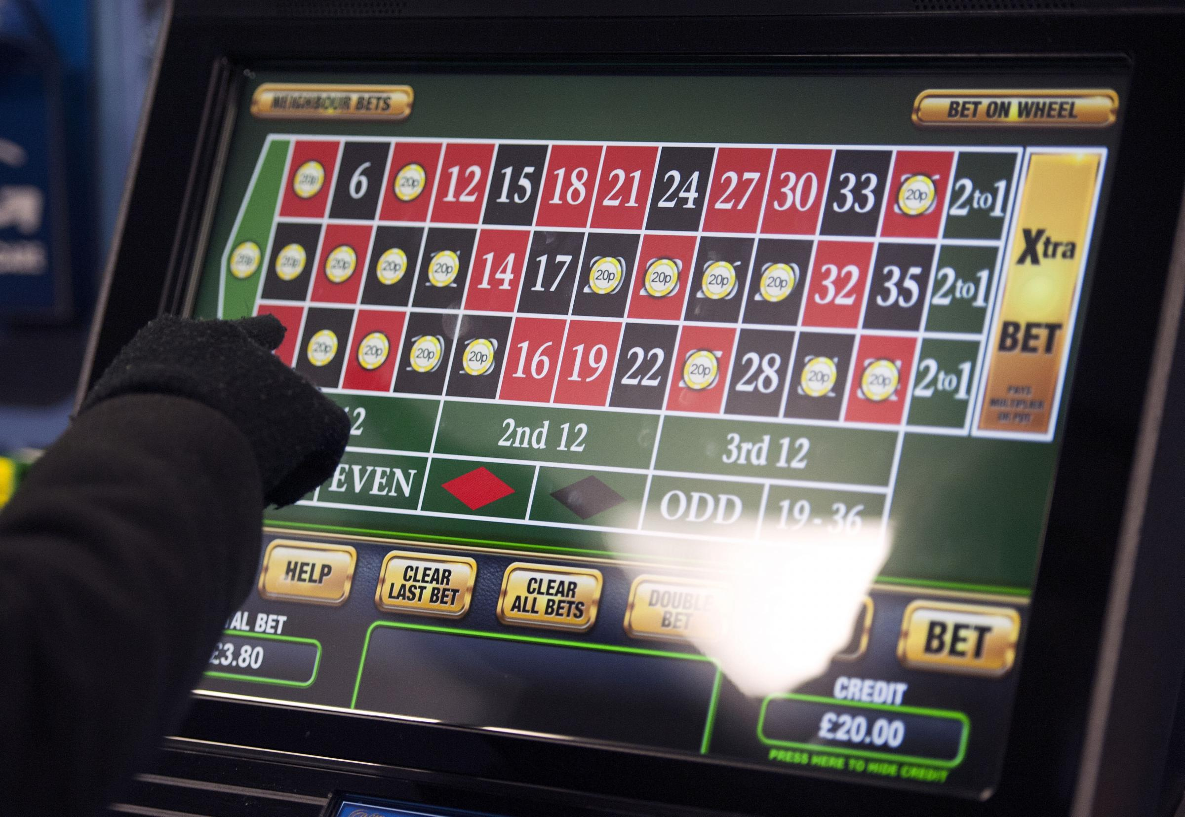 File photo dated 12/01/13 of a someone using a gambling machine. Bookmakers are nervously awaiting an official announcement on whether the Government will slash the amount people can stake on fixed-odds betting terminals (FOBTs)..