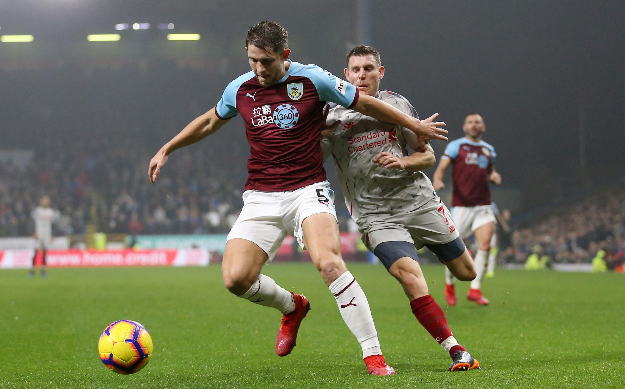Burnley's James Tarkowski (left) and Liverpool's James Milner battle for the ball  during the Premier League match at Turf Moor, Burnley. PRESS ASSOCIATION Photo. Picture date: Wednesday December 5, 2018. See PA story SOCCER Burnley. Photo credit