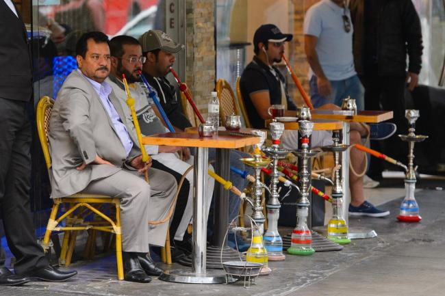 General view of customers smoking shisha pipes outside a cafe (Dominic Lipinski/PA)