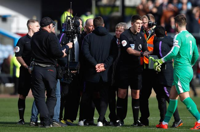 Tottenham Hotspur manager Mauricio Pochettino (centre) and his staff speak to referee Mike Dean and the match officials after the Premier League defeat to Burnley last month