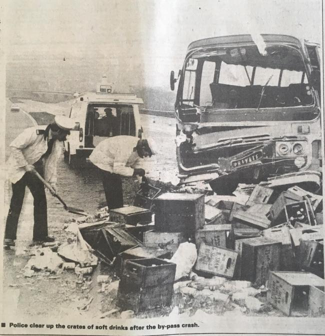 Police clear up the crates of soft drinks after the bypass crash (LET: March 4, 1982)