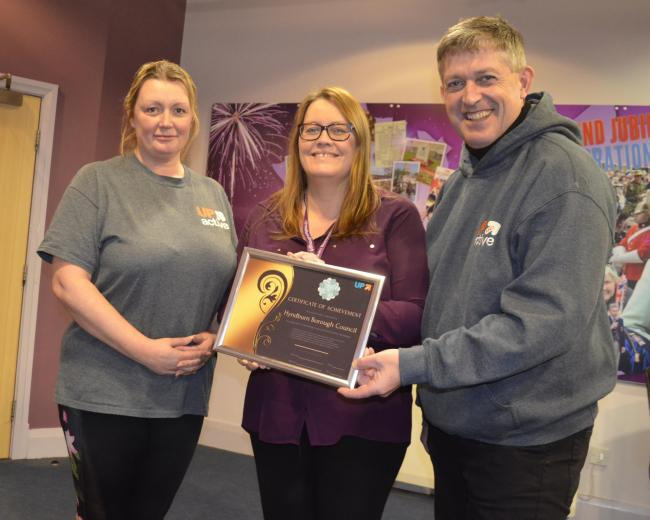 Marie Rae from Hyndburn Leisure presents Hyndburn Council HR Manager, Joanne Wolfendale and Hyndburn Council Leader Cllr Miles Parkinson with the Up and Active Gold Award.