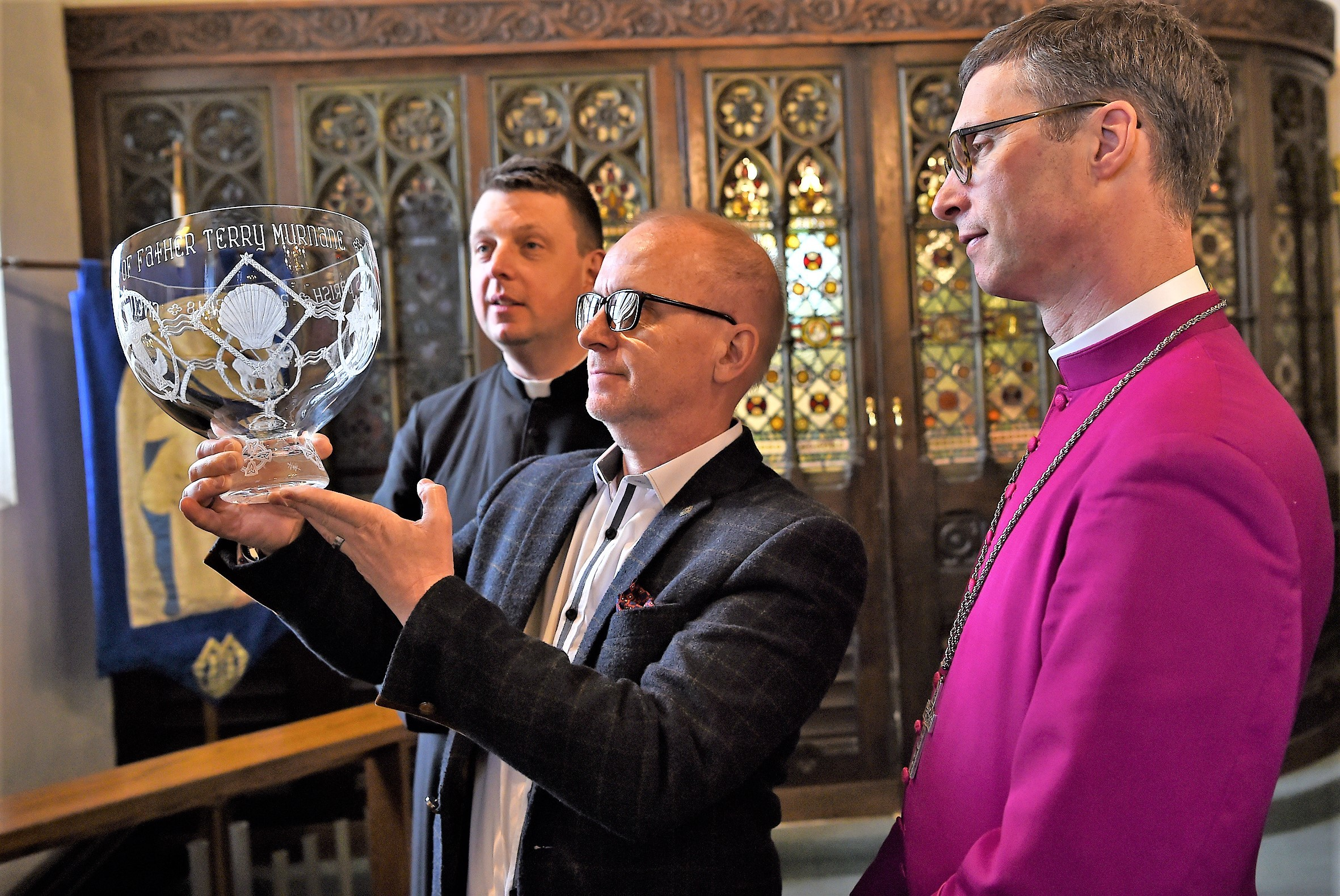 Artist Alexis Valentine holds one of the baptismal bowls as Father David Stephenson (left) and Bishop Philip look on